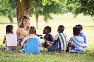 Children and education, teacher reading book to young students